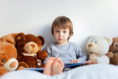 Little boy, sitting in bed, reading a book Royalty Free Stock Images