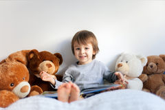 Little boy, sitting in bed, reading a book Royalty Free Stock Image