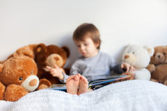 Little boy, sitting in bed, reading a book Stock Images