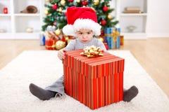 Little boy sitting behind big present. Little boy sitting behind big Christmas present box Royalty Free Stock Photos