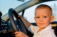 Little boy sitting behind the wheel of a car Royalty Free Stock Photo