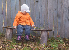 Little boy sitting on a bench Stock Image