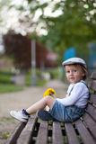 Little boy, sitting on a bench Stock Photos