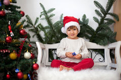 Little boy, sitting on a bench under christmas tree, eating choc Stock Images