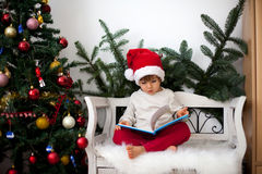Little boy, sitting on a bench under christmas tree, eating choc Royalty Free Stock Photos