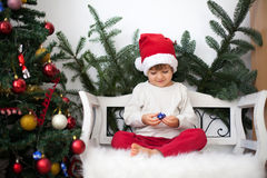 Little boy, sitting on a bench under christmas tree, eating choc Royalty Free Stock Photography