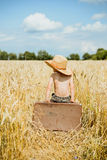 Little boy sitting on big old valize in summer. Little kid sitting on big old brown leather suitcase in summer countryside. Child with valize wearing straw hat Royalty Free Stock Image