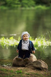Little boy sitting on big stone near water Stock Images