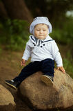 Little boy sitting on big stone near water Royalty Free Stock Photo