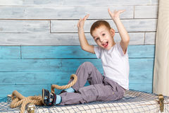 Little boy sitting on the box, lifting his hands up rejoices Royalty Free Stock Photography