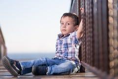 Little boy sitting on the bridge Stock Image