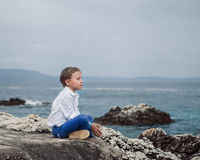 Little boy sitting calm on the solitade sea beach Stock Image