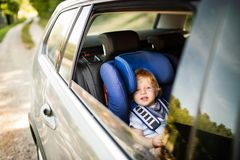 Little boy sitting in the car seat in the car. Royalty Free Stock Photos