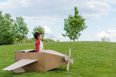 Little boy sitting in cardboard toy plane and looking away in park Stock Image