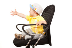 Little boy sitting on a chair Stock Photos