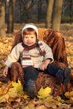 Little boy sitting in chair outdoors Royalty Free Stock Photos