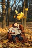 Little boy sitting in chair in park Stock Image