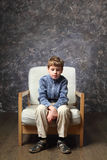 Little boy sitting on chair in studio Stock Image