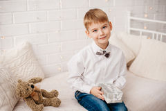 Little boy sitting with Christmas present in hands Royalty Free Stock Photos