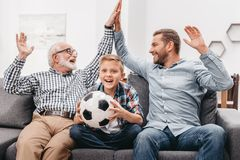 Little boy sitting on couch in living room and holding soccer ball, while his father and grandfather are high-fiving. Each other stock photography
