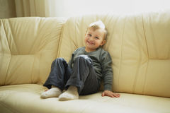 Little boy sitting on couch royalty free stock photography