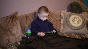 Little boy sitting on the couch and watching a cartoon on smartphone stock footage