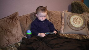 Little boy sitting on the couch and watching a cartoon on smartphone stock video footage