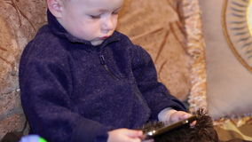 Little boy sitting on the couch and watching a cartoon on smartphone stock video