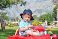 Little boy sitting on a deck chair. And looking at the camera Royalty Free Stock Photos