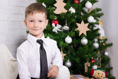 Little boy sitting in decorated living room with Christmas tree Stock Image