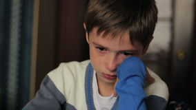 Little boy sitting at a desk crying, tears on his stock footage