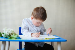 Little boy sitting at the desk draws Royalty Free Stock Photo