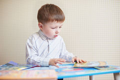 Little boy is sitting at the desk and read book.  Royalty Free Stock Image