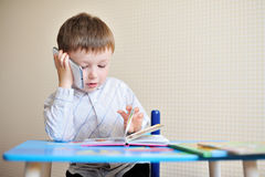 Little boy is sitting at a desk in school and speaking on the phone.  Royalty Free Stock Images