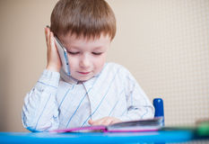 Little boy sitting at desk and talking on the phone Royalty Free Stock Photo