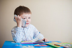 Little boy sitting at desk and talking on the phone Stock Photography