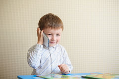 Little boy sitting at desk and talking on the phone Stock Images