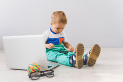 Little boy sitting with digital gadgets in studio. Playing around with tech. Boy sitting on floor near laptop and playing with his smartphone in studio Stock Photography
