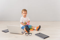 Little boy sitting with digital gadgets in studio Royalty Free Stock Photo
