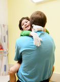Little boy sitting in doctor's office, laughing Royalty Free Stock Images