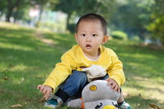Little boy sitting on the doll Stock Image