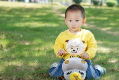 Little boy sitting on the doll Royalty Free Stock Photos