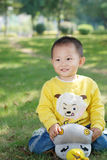 Little boy sitting on the doll Royalty Free Stock Image