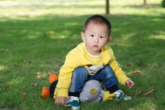 Little boy sitting on the doll Royalty Free Stock Photo