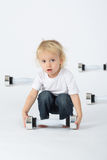 A little boy sitting with dumbbell Stock Images