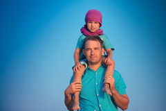 Little boy sitting on father's shoulders. Little boy sitting on a happy father's shoulders Stock Photo