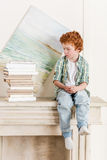 Little boy sitting on fireplace near pile of books Royalty Free Stock Images
