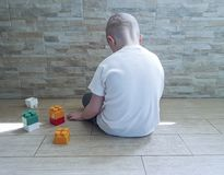 Little sad boy sitting on the floor with a block depression frustratedsadness. Little  boy sitting on the floor with a block unhappy   frustrated depression Royalty Free Stock Photos