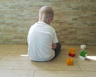 Little sad boy sitting on the floor unhappy a block depression frustratedsadness. Little  boy sitting on the floor with a block unhappy   frustrated depression Royalty Free Stock Images