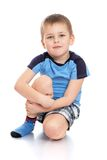 Little boy sitting on the floor clutching her knee Stock Image